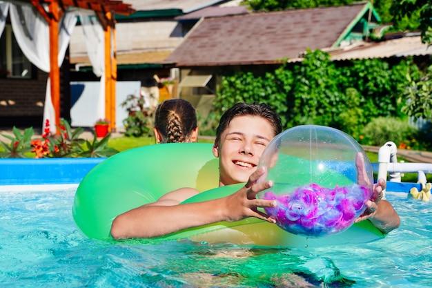 Ein junger mann spielt mit einem aufblasbaren ball im pool im hinterhof