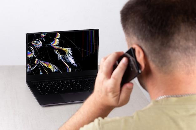 Ein junger mann spricht auf einem mobiltelefon vor einem laptop mit einem kaputten, zerbrochenen bildschirm