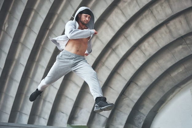 Ein junger mann springt. parkour im stadtraum, sportliche aktivität.