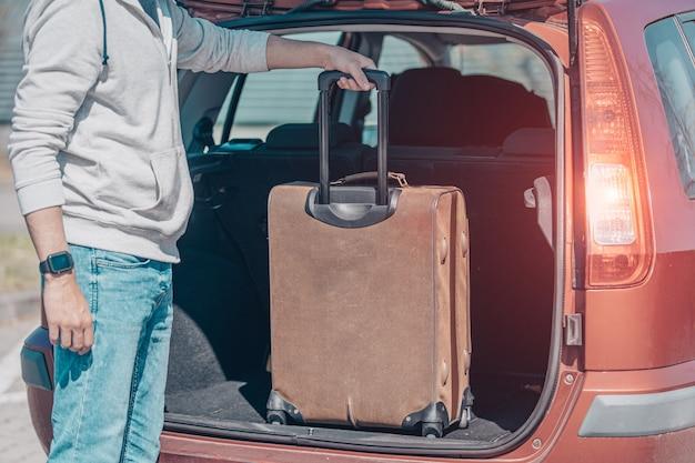 Ein junger mann steckt gepäck in den kofferraum eines autos