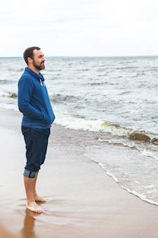 Ein junger mann steht am meer