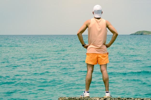 Ein junger mann steht am rand des piers und schaut in die ferne