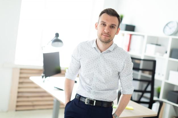 Ein junger mann steht auf einem tisch im büro gelehnt.