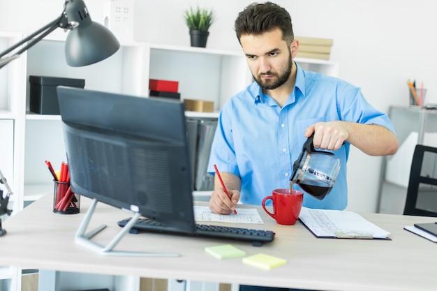 Ein junger mann steht im büro am computertisch und kocht seinen kaffee.