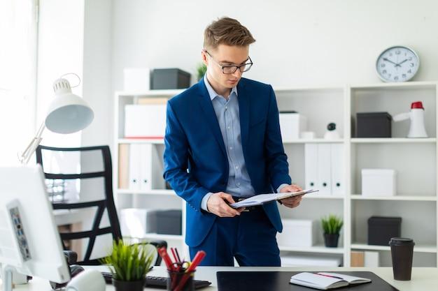 Ein junger mann steht in der nähe eines tisches im büro und hält dokumente in seinen händen.