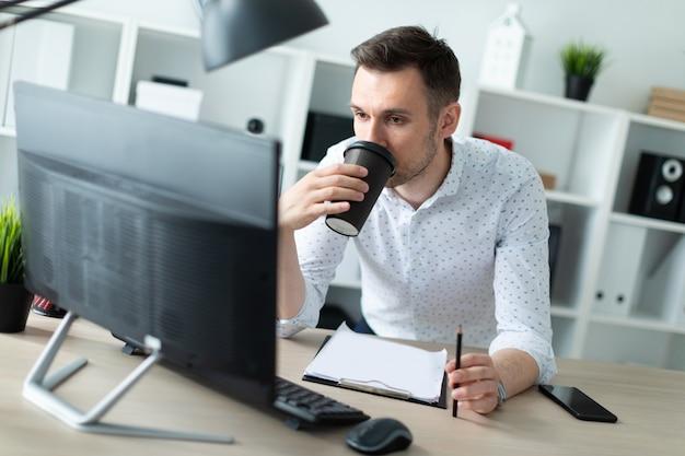 Ein junger mann steht neben einem tisch im büro, hält einen bleistift in der hand und trinkt kaffee. ein junger mann arbeitet mit dokumenten und einem computer.