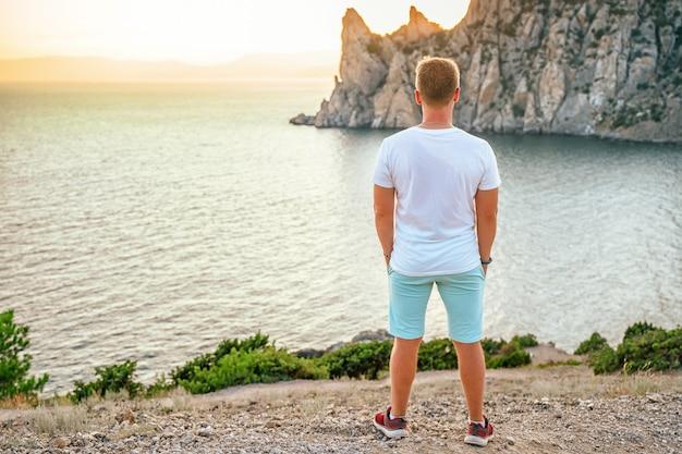 Ein junger mann tourist am kap kapchik in der krim-seelandschaft bei sonnenuntergang