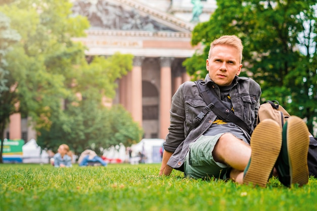 Ein junger mann tourist mit auf gras liegend vor der st. isaac kathedrale in saount petersburg