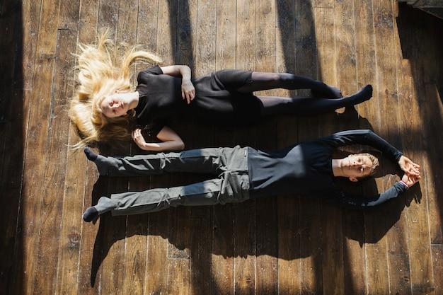 Ein junger mann und eine junge blonde frau mit langen haaren, die auf dem boden liegen. probleme und schwierigkeiten in den beziehungen. die schwierige situation im leben. konzeptfotografie. schauspieler spielen. harte schatten