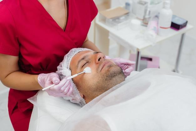 Ein junger mann unterzieht sich einem kosmetischen gesichtspeeling. kosmetologie und verjüngung.