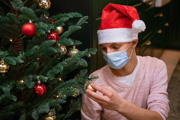 Ein junger mann verkleidet einen weihnachtsbaum mit einer schutzmaske und einer weihnachtsmannmütze. weihnachtsferien während einer pandemie
