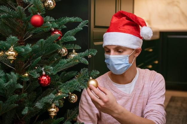 Ein junger mann verkleidet einen weihnachtsbaum mit schutzmaske und weihnachtsmann-hut.