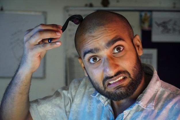 Ein junger mann verwendet dermaroller für das haarwachstum