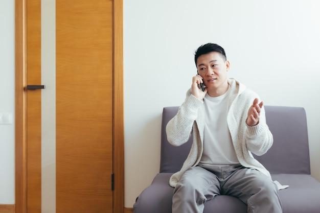 Ein junger mann wartet im flur einer klinik oder eines bürozentrums, telefoniert und teilt neuigkeiten und das ergebnis des interviews, ernst in alltagskleidung