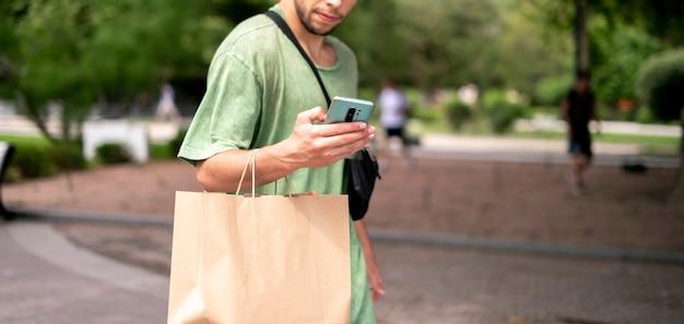Ein junger mann zieht mit einer papiertüte in die stadt, produktlieferung