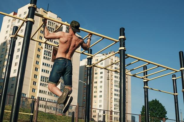 Ein junger mann zieht sich auf dem sportplatz hoch, ein athlet, der draußen in der stadt trainiert