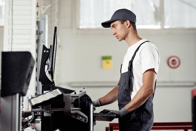 Ein junger mechaniker schaut auf einen computerbildschirm und sucht nach fehlern in einem auto.
