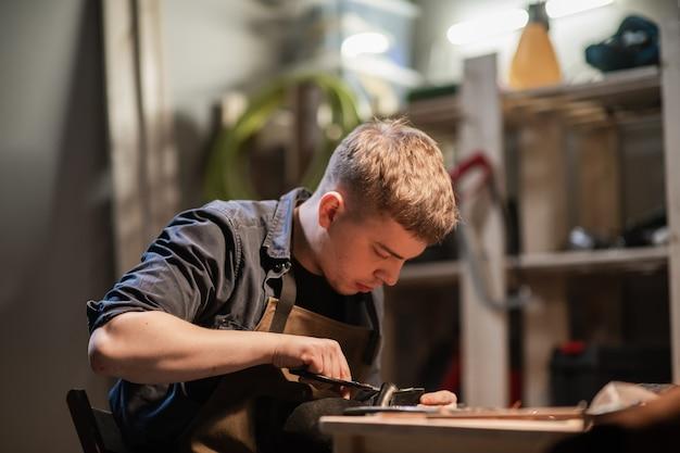 Ein junger meister in der manuellen herstellung von schuhen in seiner werkstatt arbeitet an der herstellung von schuhen.