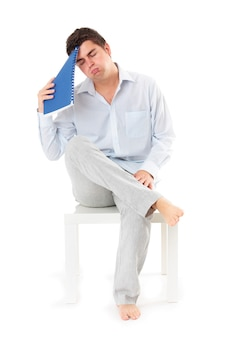 Ein junger müder geschäftsmann, der auf weißem hintergrund sitzt