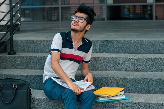 Ein junger nachdenklicher student in einem t-shirt sitzt mit büchern auf der treppe und schaut nach vorne