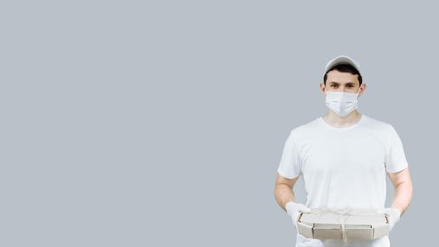 Ein junger pizzabote in schutzmaske und handschuhen verteilt kisten mit lebensmitteln und liefert während einer epidemie ein coronavirus