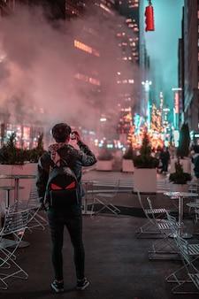 Ein junger reisender, der mit seinem handy an vielen weihnachtslichtern ein foto macht