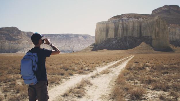 Ein junger reisender trinkt wasser gegen die felsen