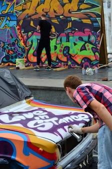 Ein junger rothaariger graffitikünstler malt ein neues buntes graffiti auf das auto.