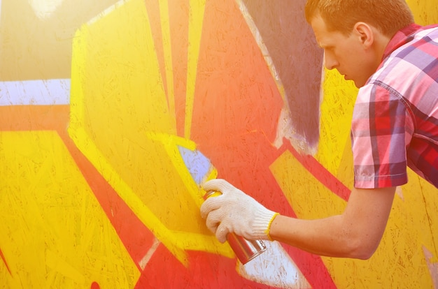 Ein junger rothaariger graffitikünstler malt ein neues graffiti an die wand