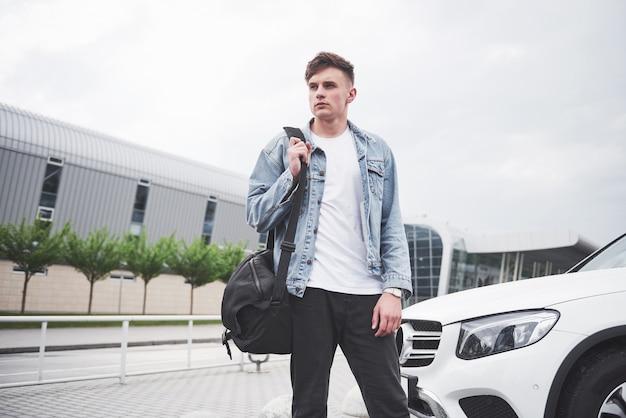 Ein junger schöner mann am flughafen wartet auf den flug.