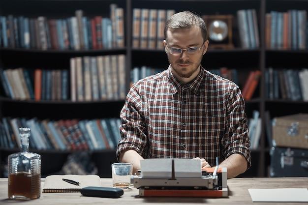 Ein junger schriftsteller schreibt auf einer alten schreibmaschine vor dem hintergrund eines bibliotheksschrankes ein buch.