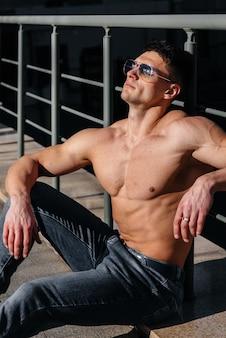 Ein junger sexy athlet mit perfekten bauchmuskeln posiert an einem sonnigen tag oben ohne in jeans draußen. gesunder lebensstil, richtige ernährung, trainingsprogramme und ernährung zur gewichtsreduktion.