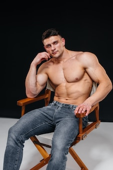 Ein junger sexy athlet mit perfekten bauchmuskeln posiert im studio oben ohne in jeans im hintergrund. gesunder lebensstil, richtige ernährung, trainingsprogramme und ernährung zur gewichtsreduktion.
