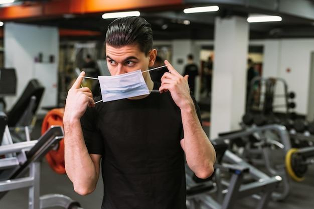 Ein junger sportler setzt im fitnessstudio eine schutzmaske auf
