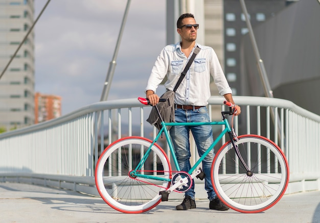 Ein junger stilvoller mann mit der sonnenbrille, die nahe bei seinem fahrrad aufwirft.