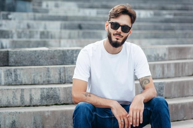 Ein junger stilvoller mann mit einem bart in einem weißen t-shirt und einer brille
