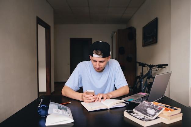 Ein junger student benutzt während des studiums ein telefon. zu hause unterrichten.