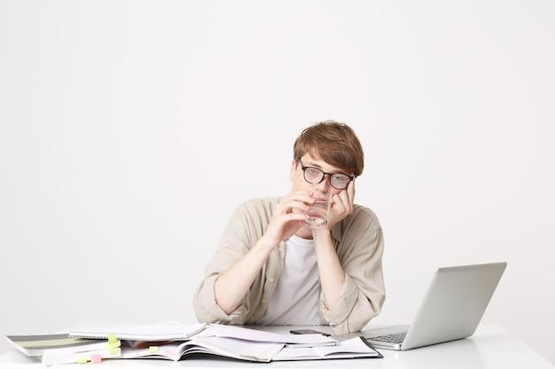 Ein junger student, der am tisch sitzt, sieht sehr müde aus