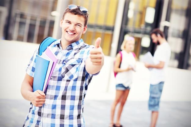Ein junger student, der auf dem campus ein ok-schild zeigt showing