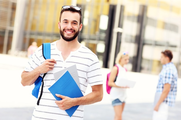 Ein junger student, der auf dem campus steht und lächelt
