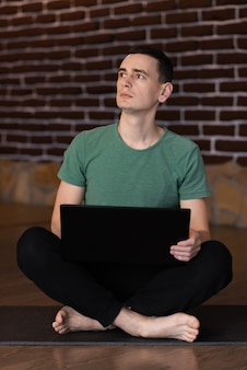 Ein junger student, der erstaunt aussieht, während er spät in der nacht zu hause einen laptop benutzt