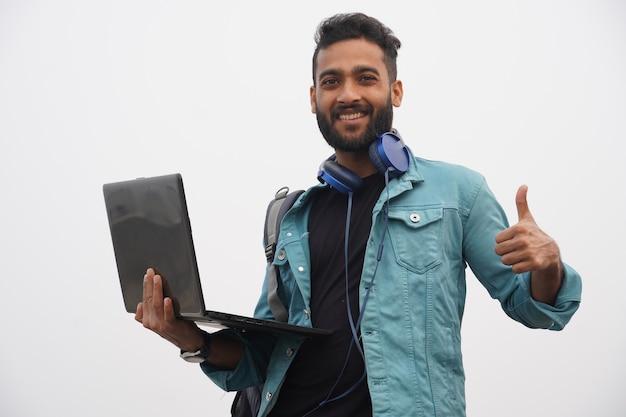 Ein junger student, der mit laptop und kopfhörer tumnbs aufgibt