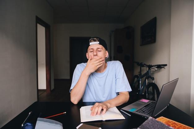 Ein junger student gähnt beim lesen eines buches. der student will schlafen. hausaufgaben. zu hause unterrichten.