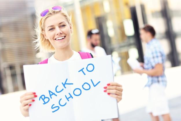 Ein junger student steht auf dem campus mit einem offenen notizbuch und zurück zur schulinschrift