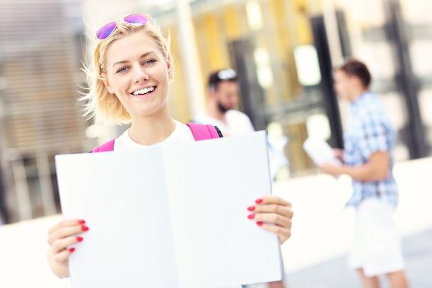 Ein junger student steht mit einem offenen notebook auf dem campus