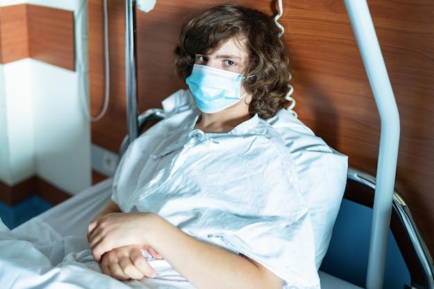 Ein junger teenager mit schutzmaske sitzt in einem krankenhausbett auf einer station. coronavirus infektion. kind, das ernsthaft in die kamera schaut. dringender krankenhausaufenthalt.