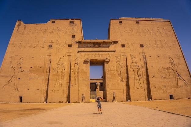 Ein junger tourist am eingang zum edfu-tempel in der nähe des nils in assuan. ägyptisch