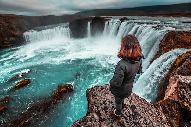 Ein junger tourist, der den godafoss-wasserfall von oben betrachtet. island