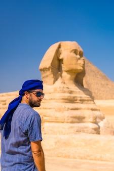 Ein junger tourist, der die große sphinx von gizeh in blauem und blauem turban genießt und bewundert. kairo, ägypten