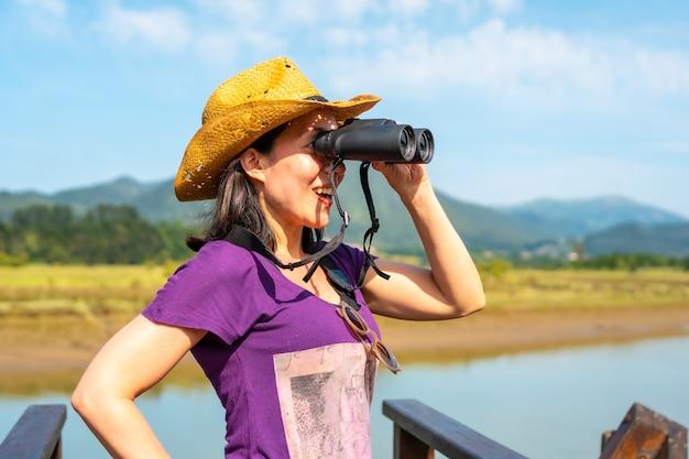 Ein junger tourist, der vögel mit einem fernrohr von den hölzernen piers der urdaibai-sümpfe aus betrachtet, einem biosphärenreservat in bizkaia neben mundaka. baskenland
